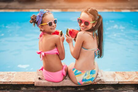 Pleased little girls with slices of watermelon at poolside in sunny summer day