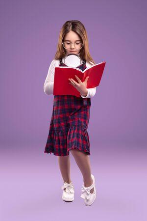 Smart schoolgirl with magnifier reading book