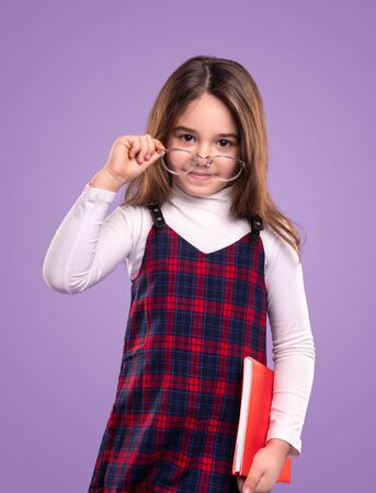Adorable schoolgirl with textbook adjusting glasses
