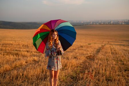 Young woman with umbrella standing in field in evening Banco de Imagens - 143046396