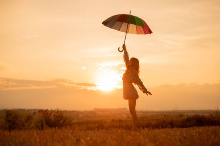 Young woman with umbrella standing in field at sunset Banco de Imagens - 143046420