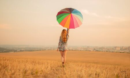 Stylish woman with umbrella walking in golden field Banco de Imagens - 143073074