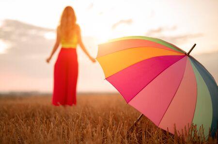 Woman with umbrella enjoying sunset in countryside Banco de Imagens - 143046411