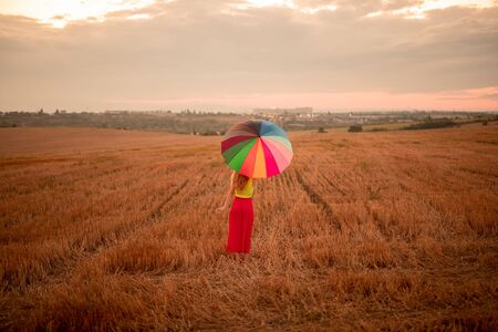 Young woman with multicolored umbrella standing in field Banco de Imagens - 143073090