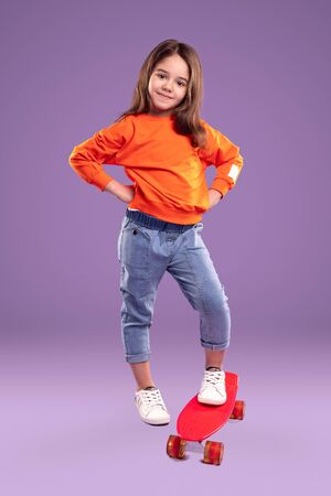 Stylish little sporty girl with vivid red skateboard