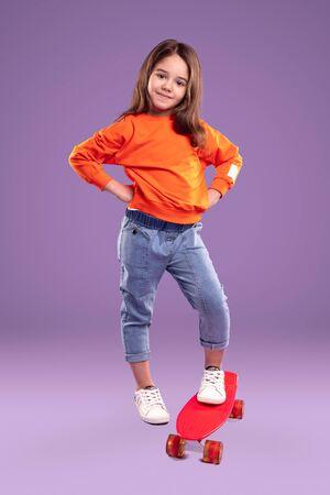 Stylish little sporty girl with vivid red skateboard Banco de Imagens - 143073103