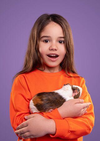 Amazed girl hugging guinea pig Banco de Imagens - 143073107