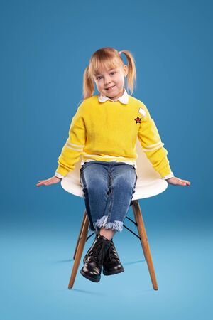 Cute little girl sitting on chair and smiling at camera Banco de Imagens - 143073113