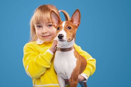 Adorable little girl holding dog and looking at camera Banco de Imagens - 143073116