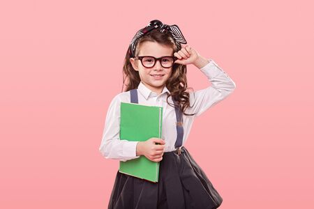 Smart schoolgirl adjusting trendy glasses Banco de Imagens
