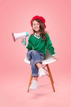 Little leader with loudspeaker sitting on chair Banco de Imagens - 143073123