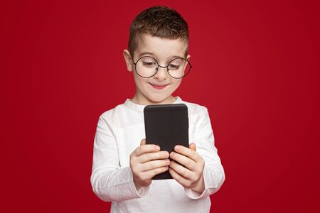 Little boy using modern smartphone Banco de Imagens - 143046529