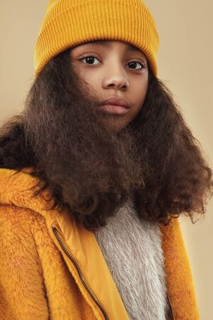 Modern African American female teenager with long curly hair wearing trendy yellow coat and knitted hat against beige background Banco de Imagens - 143073142