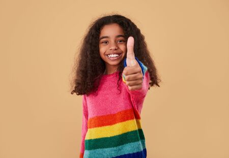 Positive African American schoolgirl in colorful sweater smiling and showing thumb up while standing against beige background Banco de Imagens - 143073143