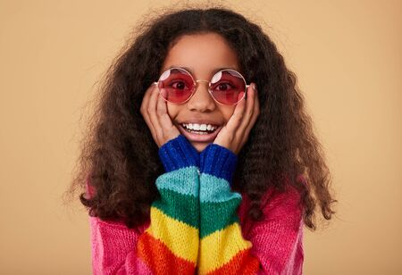 Surprised ethnic girl in rainbow sweater