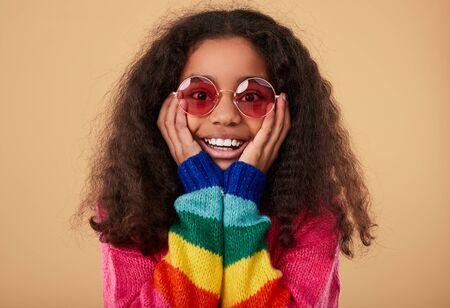 Surprised ethnic girl in rainbow sweater Banco de Imagens - 143047375