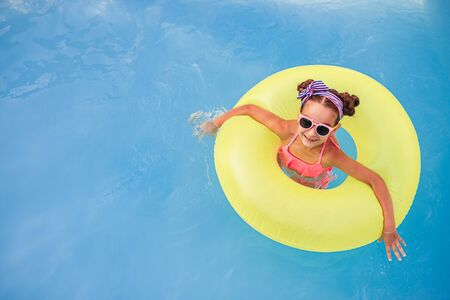 Cheerful girl with inflatable ring having fun in pool Banco de Imagens - 143073149