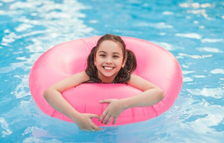 Happy girl with inflatable ring enjoying pool of resort Banco de Imagens - 143073151