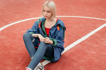 Stylish teenager sitting on sports ground Banco de Imagens - 143046786