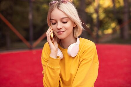 Female teenager answering phone call on street