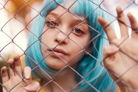 Teen girl in blue wig standing behind fence Banco de Imagens