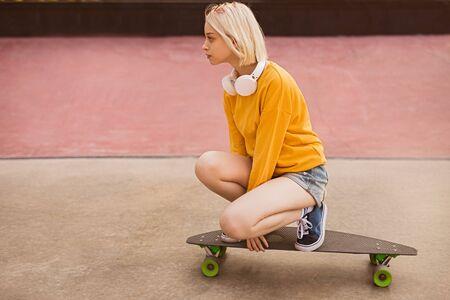 Teen girl riding skateboard on street Banco de Imagens - 143073184