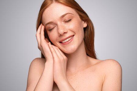 Freckled young woman enjoying clean skin Banco de Imagens - 143073206