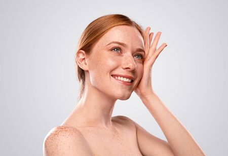Charming redhead female with naked shoulders on gray background Banco de Imagens - 143073187