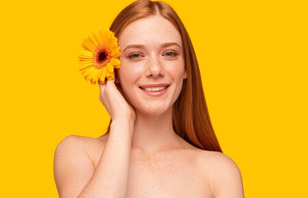 Young ginger model with flower smiling at camera
