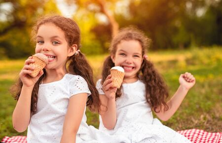 Happy sisters eating ice cream in park Banco de Imagens
