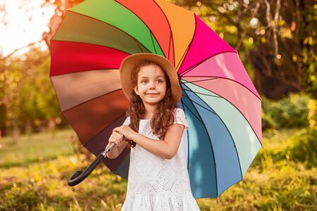 Cute girl with umbrella in garden