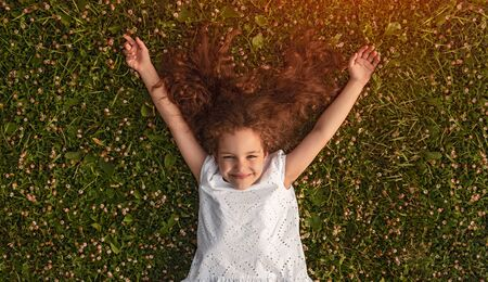 Cheerful little girl lying on green grass