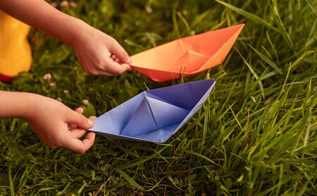 Side view of crop children holding bright orange and purple paper boats over green grass while playing together in countryside Banco de Imagens - 143046974