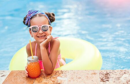 Cute little girl with juice enjoying summer day in pool Banco de Imagens - 143073204