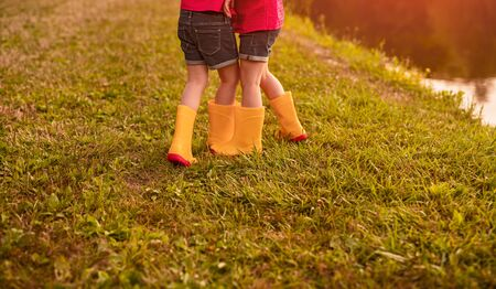 Back view of crop anonymous little girls in similar clothes and orange gumboots having fun together while playing near pond in summer day