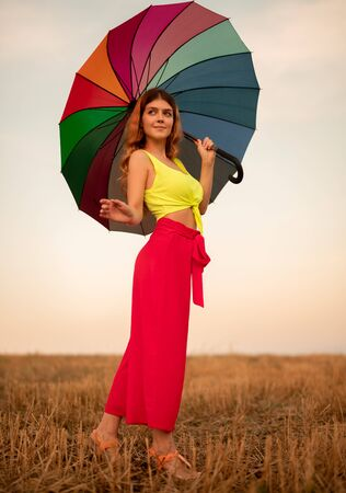 Graceful woman with umbrella walking in field