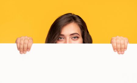 Woman hiding behind empty banner
