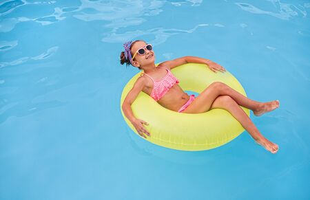 Happy child lounging on float in pool 版權商用圖片
