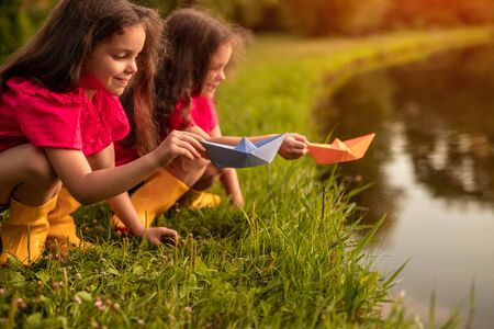 Sisters playing with paper boats near lake