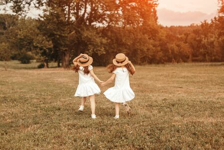 Back view of unrecognizable sisters in similar outfits holding hands and running on grass while playing in summer park together