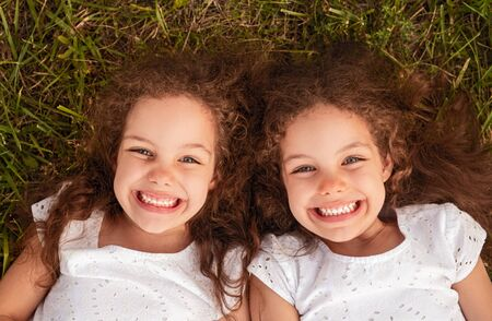 Cheerful sisters lying on grass