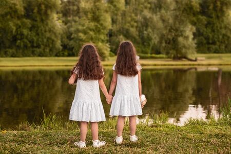 Back view of unrecognizable girls in similar white dresses holding hands and admiring calm lake while resting on grassy shore in summer park together