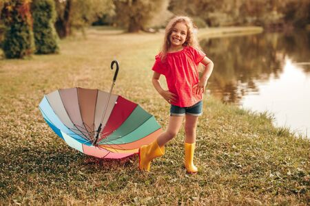 Full body cheerful child with hands on waist smiling and looking at camera while standing near colorful umbrella ,on pond coast on summer day in park