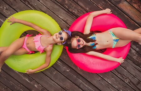 Cheerful girls lying on inflatable rings