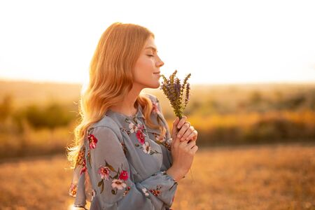 Young woman enjoying smell of flowers in evening