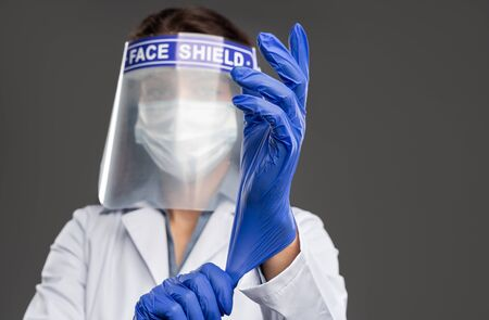 Medical practitioner putting on protective wear