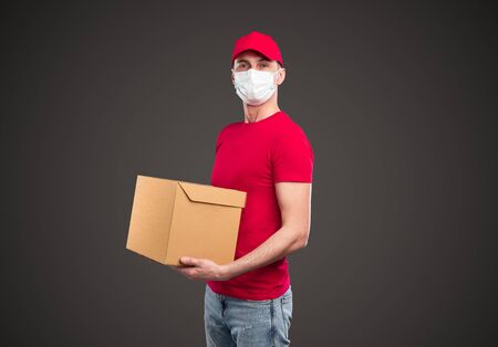 Delivery man in mask carrying carton box Banco de Imagens