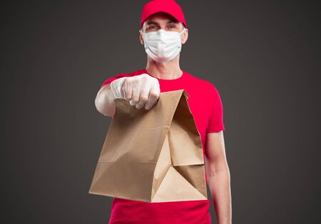 Delivery employee in protective mask and gloves holding bag with order