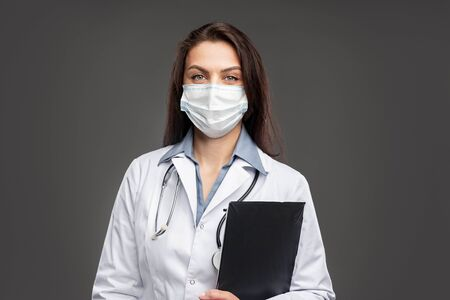 Female doctor in face mask with clipboard