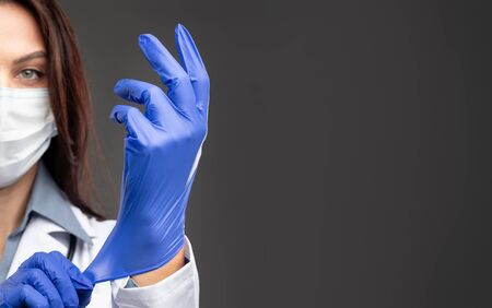 Crop female doctor putting on medical gloves Banco de Imagens